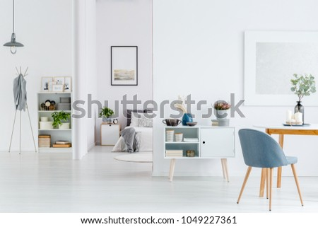 Grey chair at wooden table in white open space interior with poster on the wall and bright bedroom #1049227361