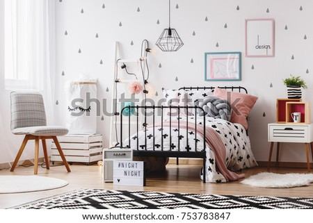 Grey chair in girl's bedroom with geometric carpet and pink and grey pillow on bed #753783847