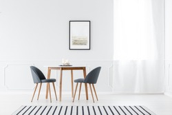 Grey chairs at wooden table in minimalist white dining room interior with poster and window