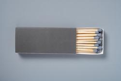 grey color matchbox and grey match sticks on a grey background