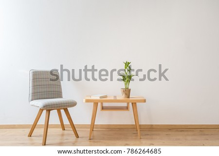 Grey comfy chair standing next to a small table with a book and a plant on it in a day room interior