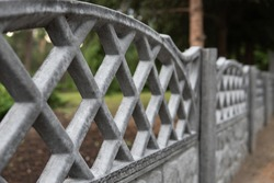 Grey concrete decorative fence somewhere in the park. Blurred green vegetation and tree on the background. Selective focus. Outside landscape