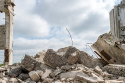 Grey concrete fragments of the Foundation against the background of a destroyed building against the sky. Background.