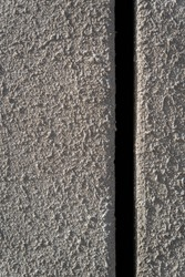 Grey concrete texture. Rough wall. Hard rough material. Black vertical bar. A bar for inserting a text image. Textured concrete surface. Abstract stone background.