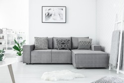 Grey corner couch with three patterned pillows standing in bright living room interior with painting and white rug