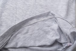 Grey cotton fabric close up. hem tee shirts, dress hem. fabric stitching.