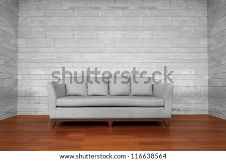 Grey couch chair on brown wooden floor and white wall