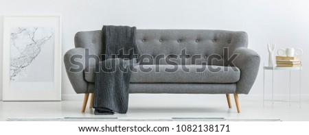 Grey couch with dark blanket standing in bright interior with metal table and simple poster #1082138171