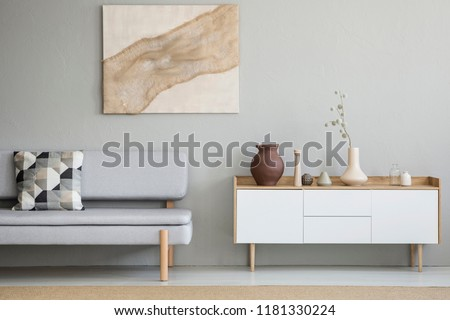 Grey couch with patterned cushion standing in real photo of bright sitting room interior with white cupboard with decor and poster with fabric hanging on the wall
