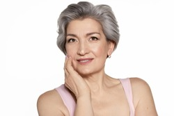 Grey-haired beautiful senior woman portrait on white copy space. Charming aged mature lady touch perfect skin on cheek. Anti-wrinkle facial care and cosmetics for elderly. Perfect appearance and age