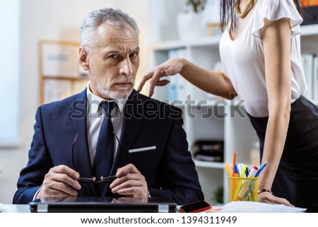 Grey-haired busy boss. Skinny long-haired woman in white shirt seducing her strict workmate while he taking off glasses #1394311949