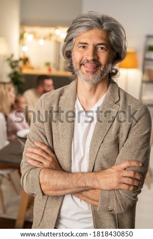 Grey-haired cheerful bearded man in casualwear crossing his arms by chest while standing in front of camera while his family having festive dinner stock photo