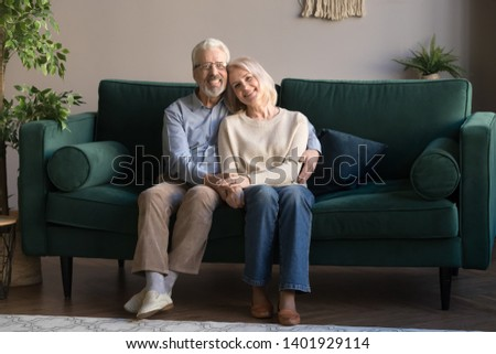 Grey haired couple in love embracing sitting on couch smiling looking at camera feels healthy, harmony in relationships, happy long life together, anniversary, older people services insurance concept