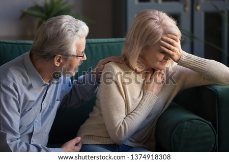 Grey haired husband helping overcome problem, supporting unhappy mature wife at home, sitting on couch, middle aged woman suffering from headache, having health problem, crying after quarrel with man