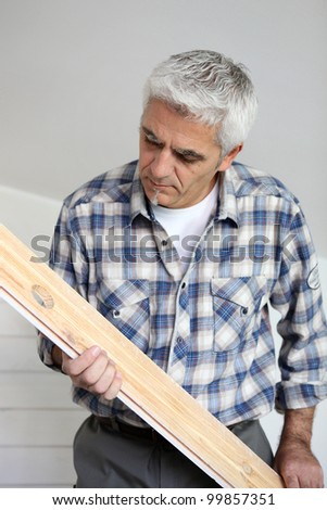 Grey-haired man holding an d examining plank of wood