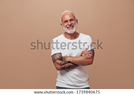 Grey haired man in white T-shirt poses on beige background. Handsome guy with beard in tattoos in bright clothes have fun into camera Photo stock ©