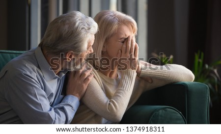 Grey haired man supporting crying unhappy mature woman, health problem, disease, bad news, loving middle aged husband hugging old wife by shoulders, sitting on couch at home, horizontal banner