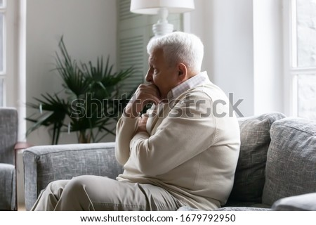Grey haired old man sit on couch in living room alone, lost in sad pessimistic thoughts related to senile disease, mental disorder memory loss or dementia. Life troubles and lonely 80s person concept