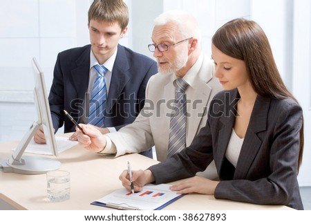 Grey-haired professor and two students discuss a task