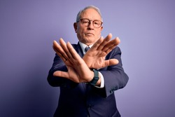 Grey haired senior business man wearing glasses and elegant suit and tie over purple background Rejection expression crossing arms and palms doing negative sign, angry face