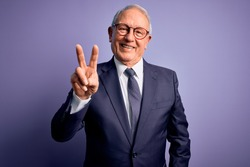 Grey haired senior business man wearing glasses and elegant suit and tie over purple background smiling looking to the camera showing fingers doing victory sign. Number two.