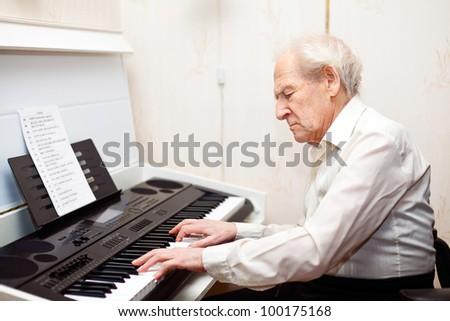 grey-haired senior man playing piano