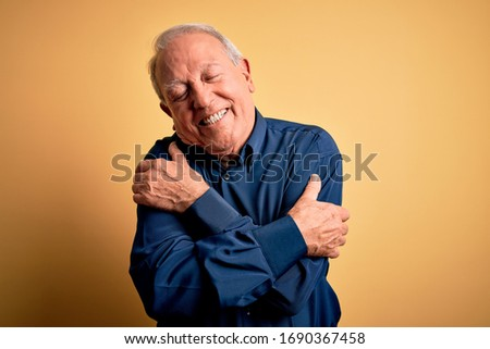Grey haired senior man wearing casual blue shirt standing over yellow background Hugging oneself happy and positive, smiling confident. Self love and self care Сток-фото ©