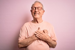 Grey haired senior man wearing glasses standing over pink isolated background smiling with hands on chest with closed eyes and grateful gesture on face. Health concept.
