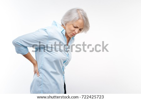 Grey-haired woman suffering from pain in lower back