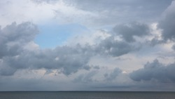 Grey high layered grey epic clouds on blue sky above thin sea water line. Heaven cloudscape air view