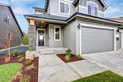 Grey home with wood siding, stone column, covered porch and two  garage spaces. Northwest, USA