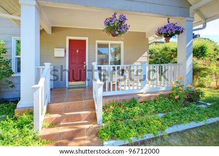 Grey house porch with red door and white railings. - stock photo