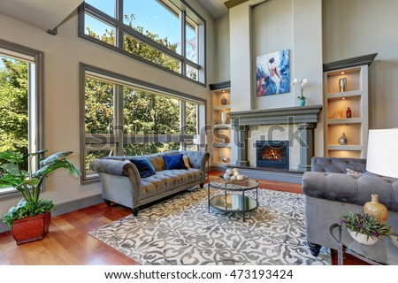Grey interior of high vaulted ceiling family room in luxury house with fireplace and large windows. Northwest, USA. #473193424