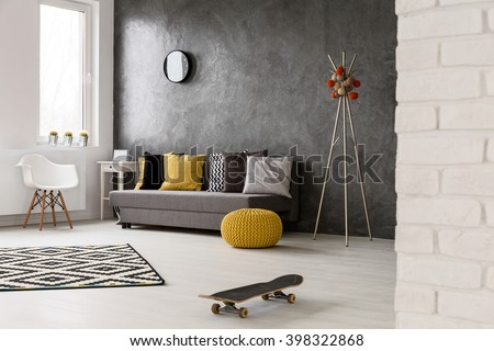 Grey interior with sofa, chair, yellow details and pattern decorations in black and white, skateboard lying on the floor  #398322868