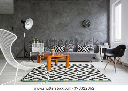 Grey interior with sofa, chairs, standing lamp, small wood table and black and white pattern decorative elements #398322862