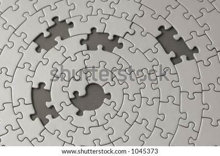 grey jigsaw with five missing pieces - focus is on the center
