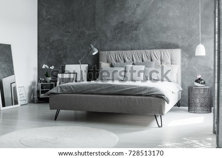 Grey king-size bed in monochromatic bedroom with mirror and white lamp above designer metal table with decorative vase #728513170