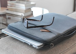 grey laptop case sitting on brown comfortable sofa protects laptop and stylish glasses. good for freelance writer who can write down ideas and prepare his work while traveling