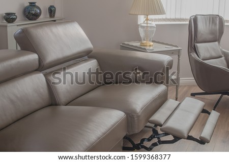 Grey Leather sofa recliner in open position in living room, with side table and single chair. ストックフォト ©
