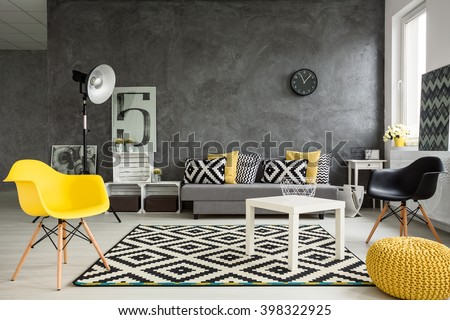Grey living room with sofa, chairs, standing lamp, small table, yellow details and pattern decorations in black and white  - Shutterstock ID 398322925