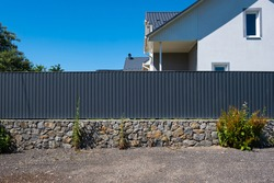 Grey metal corrugated fence in front of a residential building. Texture of profiled metal.