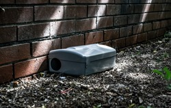Grey Metal external rodent rat bait station outside against a brick wall close up.  Pest Control.