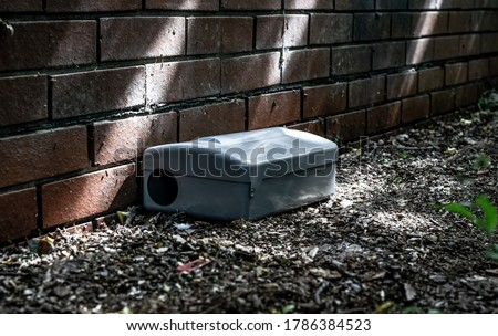 Grey Metal external rodent rat bait station outside against a brick wall close up.  Pest Control. Сток-фото ©