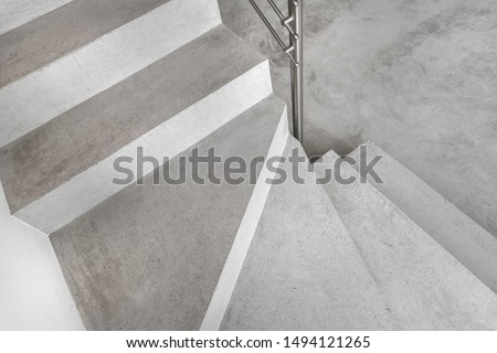 Grey microcement stairs. Stairs viewed from above. Modern design and innovative material. Metal railing.