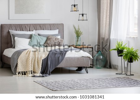 Grey, modern bedroom interior with king-size bed decorated with cushions and blankets #1031081341