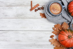 Grey mug of coffee wrapped in plaid or scarf, spices, dry oak leaves, acorns, orange pumpkins on white wooden table. Autumn drink concept. Fall, pumpkin spicy latte, thanksgiving, top, copy space