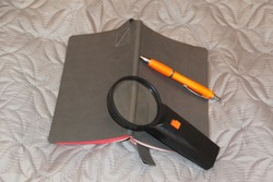 Grey notepad, ballpoint pen and magnifying glass on a light background