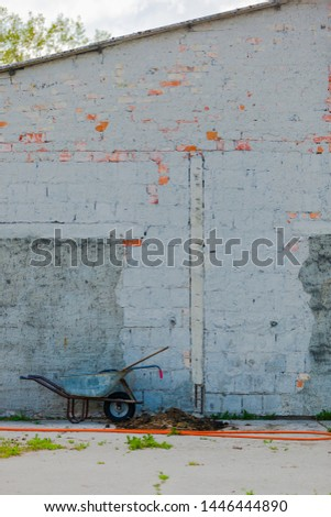 Grey painted Wall of an old Building on a Farm, with a pushcart in Front
