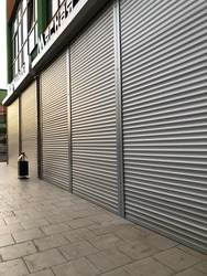 Grey roller shutters of a small storewith some sun lights on it in a town.