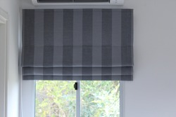 Grey roman blind with strip pattern on the window.